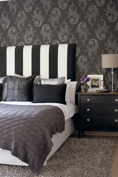 Black and white bedroom with striped headboard and a cool designed .