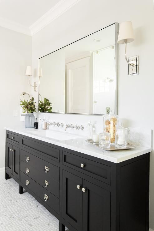 A gorgeous black bathroom vanity sits on maze marble floor tiles .