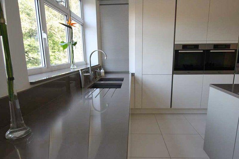 Grey kitchen tambour unit above grey quartz kitchen worktop .