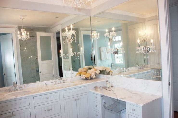 Luxurious bathroom with white beadboard vanity cabinets and drop .