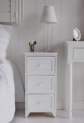Maine white wooden bedside table with 3 drawers for storage .