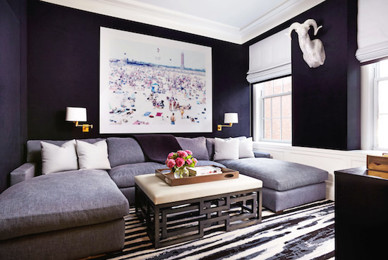 Navy blue walls with art and sconces