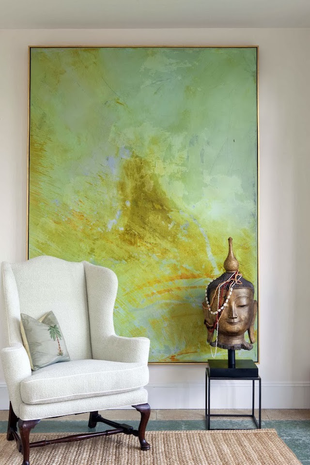 large painting behind white armchair and Buddha statue