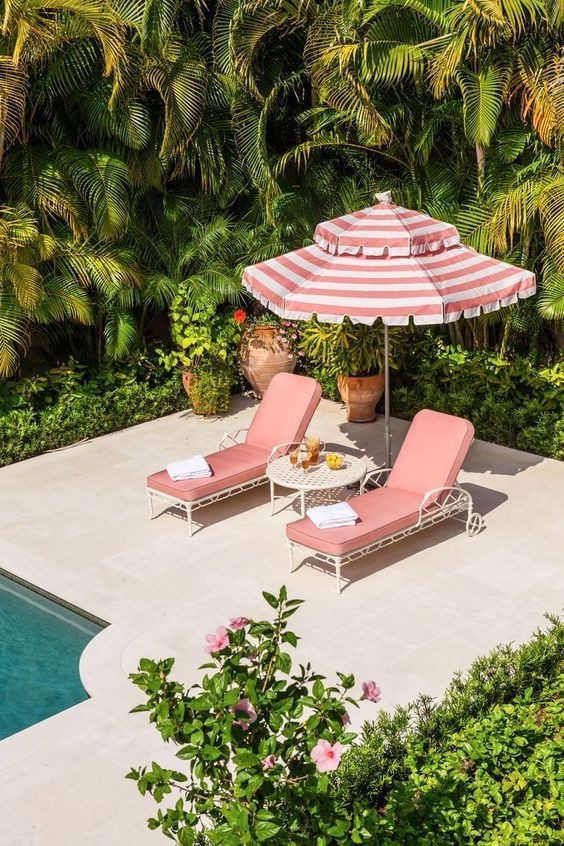 pink lounge chairs striped umbrella