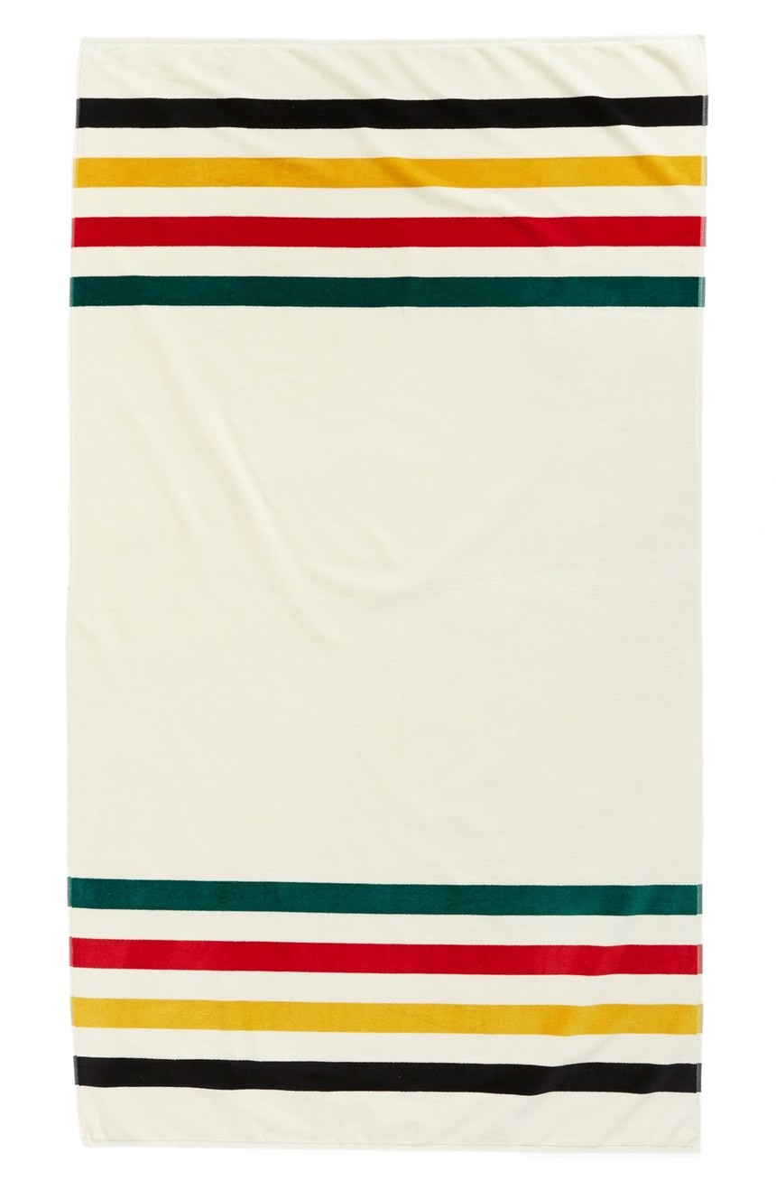 white beach towel with black yellow red green stripes