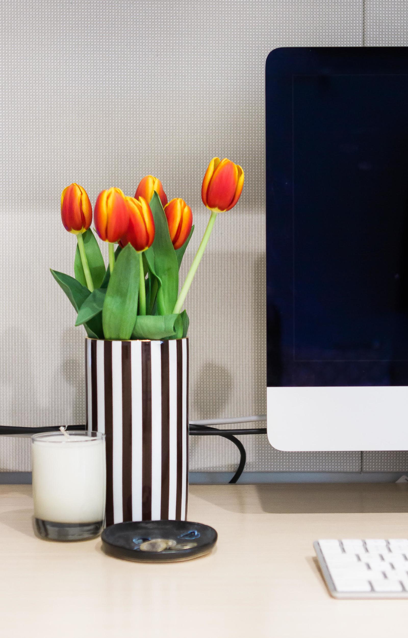 orange tulips in a striped vase