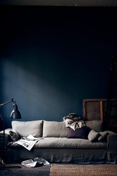 moody dark-walled room gray sofa