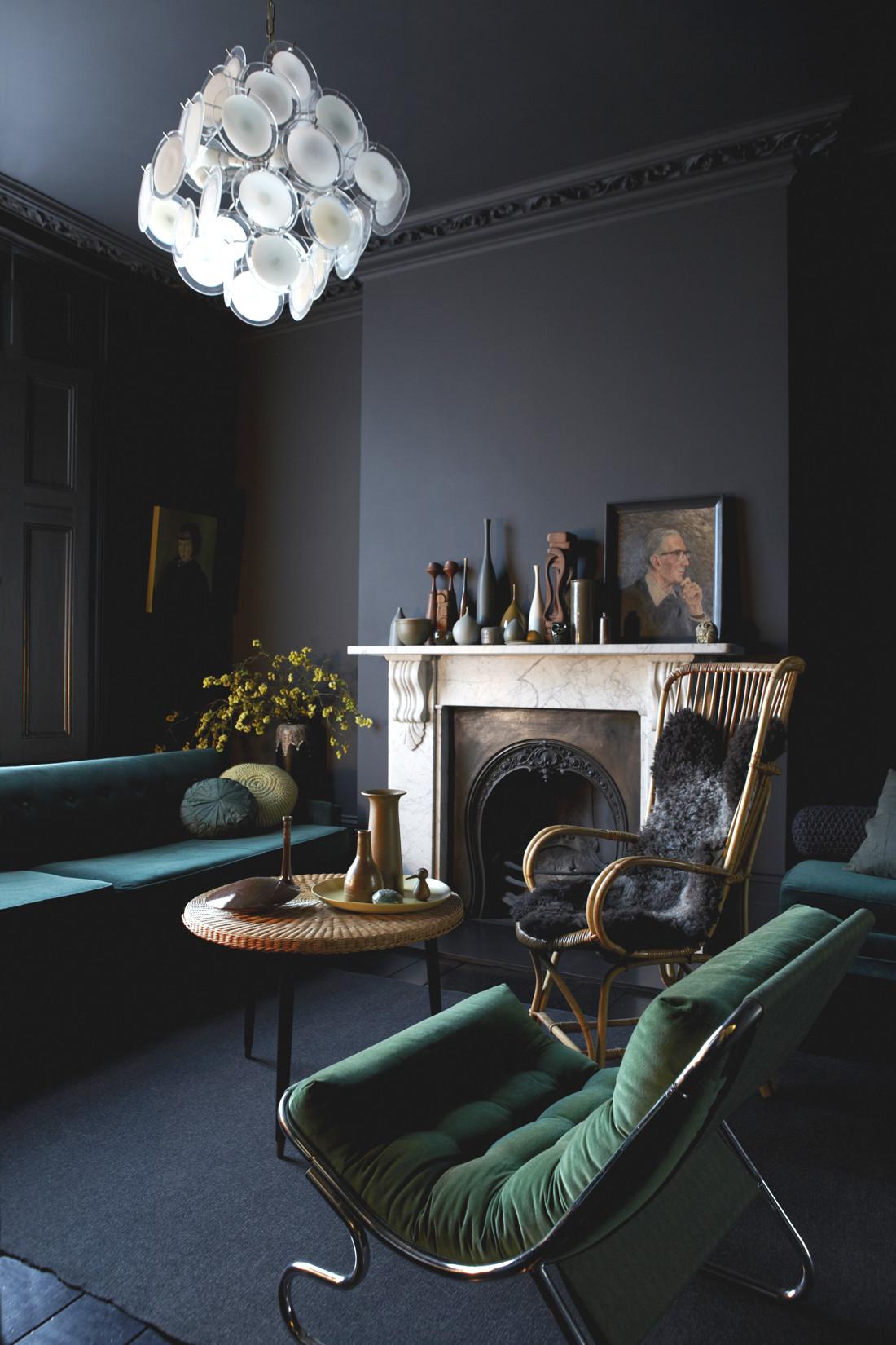 matt black walls emerald green sofa