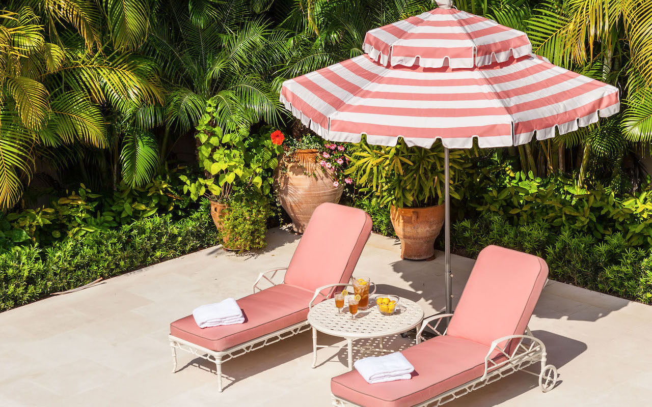 Pink deck chair with a striped umbrella